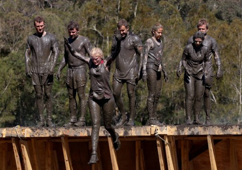 Competitors leap off a wall into a muddy pond.