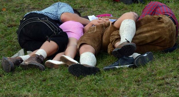 Visitors of the Oktoberfest beer festival rest on the grass.