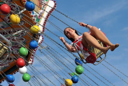 A woman wearing traditional Bavarian clothes ride a fairground carousel at the Theresienwiese Oktoberfest fair grounds in Munich.