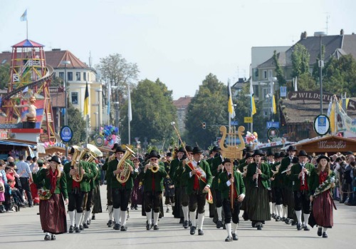 Visitors wearing traditional Bavarian clothes take part in the costumes and riflemen parade at the Theresienwiese fair grounds in Munich.