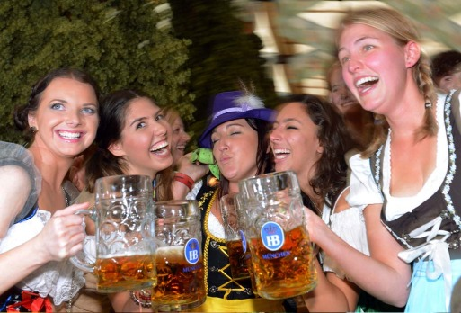 Visitors drink beer in a Oktoberfest beer festival tent.