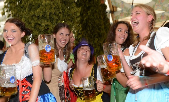 Visitors drink beer in a Oktoberfest beer festival tent at the Theresienwiese in Munich.