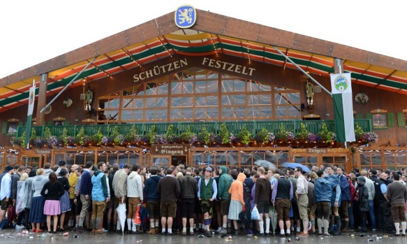 People wait in front of a Oktoberfest beer festival tent at the Theresienwiese in Munich.
