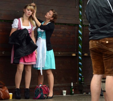 Two young women prepare their hair ahead the start of the Oktoberfest beer festival.