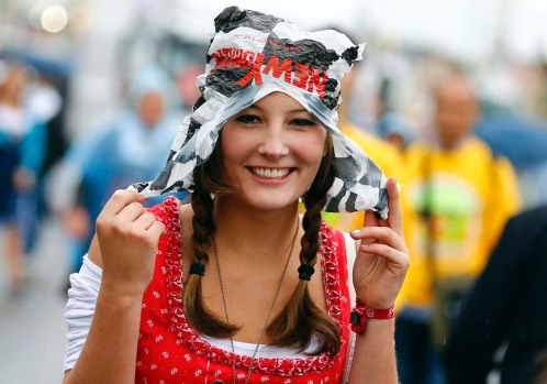 A reveller uses a plastic bag to cover herself from heavy rain on the opening day of the Munich Oktoberfest.