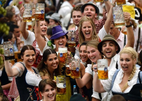 Visitors wearing traditional Bavarian clothes raise their beers in a festival tent.