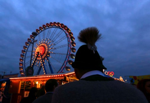 A visitor wearing a traditional Bavarian hat stands in front of a ferris wheel at the Oktoberfest in Munich.
