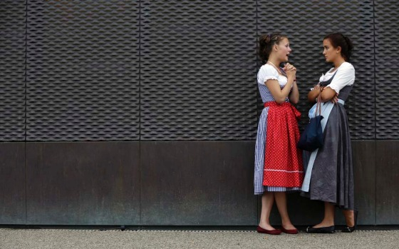 Two young women wearing in traditional Bavarian dirndl dress talk during Oktoberfestin Munich.