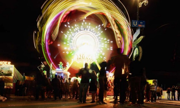 People are attracted by a luminous merry-go-round in the evening of day one of Oktoberfest beer festival.