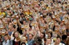 Visitors wearing traditional Bavarian clothes raise their beers in a festival tent at the start of Oktoberfest.