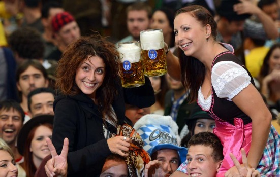 Visitors of the Oktoberfest raise their beers in a festival tent at the start of the beer festival in Munich.