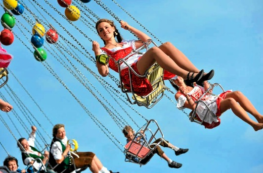 A woman wearing traditional Bavarian clothes rides a fairground carousel at the Theresienwiese Oktoberfest.