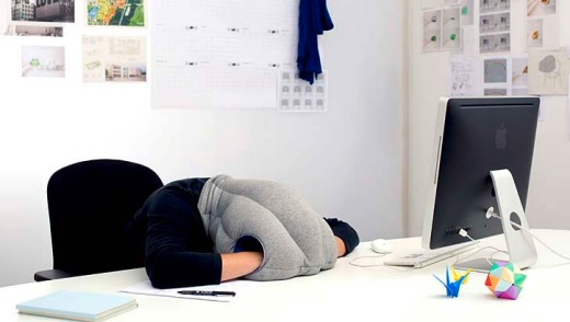 The Ostrich Pillow in use at a desk.