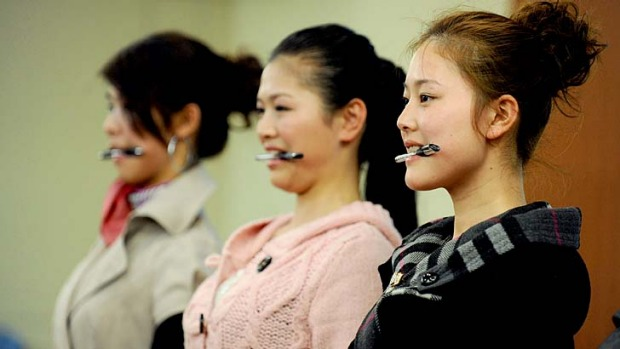 A group of young Chinese women practice standing and smiling properly during final selection to become flight ...