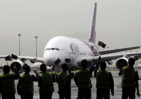 "Thai Airways staff watch the first Airbus Thai A380-800, bestowed with the royal name of ""Si Rattana,"" arrive at Bangkok's Suvarnabhumi International Airport."