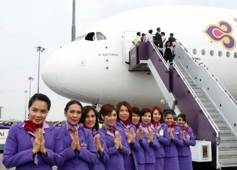 "Thai Airways crew members pose beside the first Airbus Thai A380-800, bestowed with the royal name of ""Si Rattana,"" at Bangkok's Suvarnabhumi International Airport."