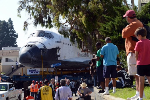 People watch as the Space Shuttle Endeavour makes its way up a narrow street as the shuttle is transported through the ...