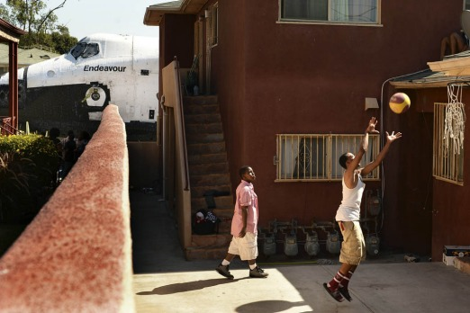 Traymond Harris (L) and Ryan Hudge play basketball as Space Shuttle Endeavour travels to the California Science Center ...