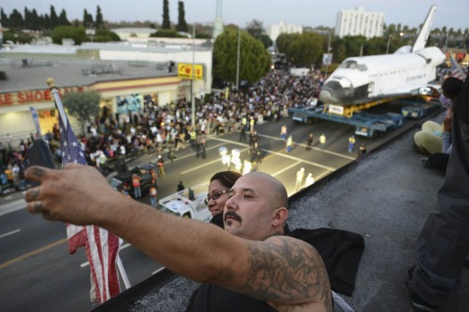 Dave Velazquez and Jennifer Barrera take a picture as the Space Shuttle Endeavour moves along Crenshaw Boulevard  in Los ...