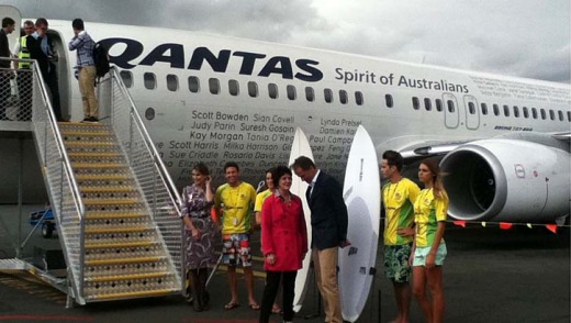 "Qantas CEO Lyell Strambi and Queensland Tourism Minister Jann Stuckey speak in front of the ""Surf Board welcoming ..."