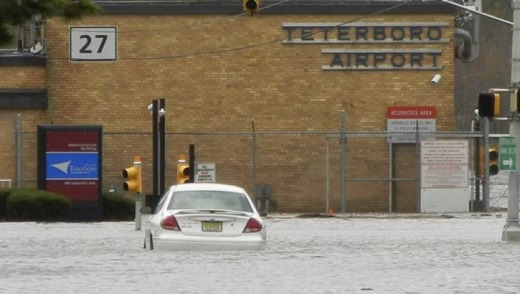 A car is partially submerged in flood waters on road leading to Teterboro Airport in Teterboro, New Jersey.