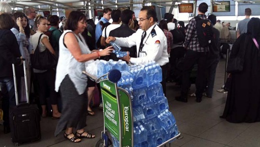 Passengers are handed water at Sydney Airport after lengthy delays.