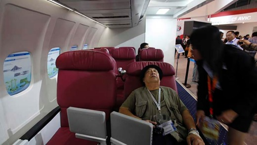 A visitor tries a business class seat in a passenger cabin model of the C919.