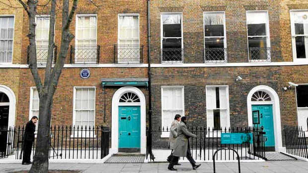 People walk past Charles Dickens' home, left, part of the Charles Dickens Museum in London.