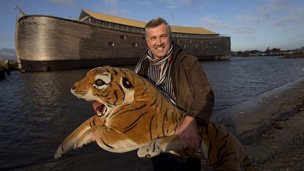 Johan Huibers poses with a stuffed tiger in front of the full scale replica of Noah's Ark.