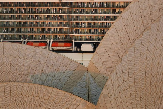 Passengers on the balconies of the Celebrity Solstice as it passes by the Sydney Opera House to dock at Circular Quay in ...