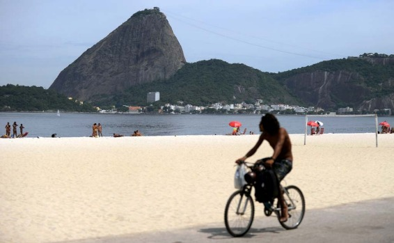 A man rides his bike in the beach in front of the Sugar Loaf Hill in Rio de Janeiro.