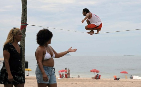 A man balances on a rope tied to two palm trees at Ipanema beach in Rio de Janeiro.