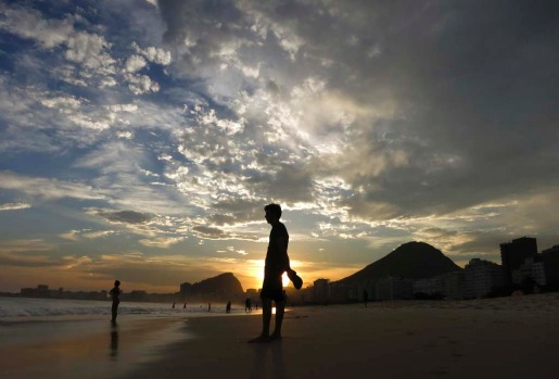A man stands in the sand during sunset at Copacabana Beach in Rio de Janeiro.