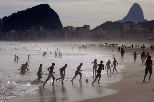 A group of boys play soccer at the edge of the surf at Copacabana Beach.