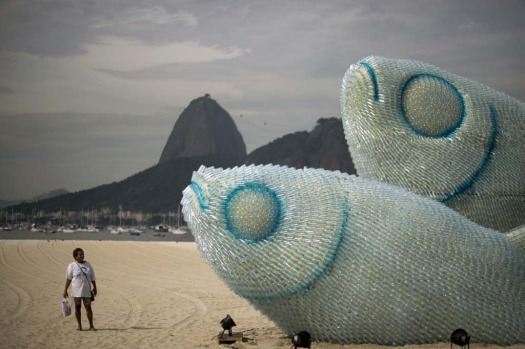 A woman looks at an installation made of recycled plastic bottles representing fishes, in Botafogo beach, in Rio de Janeiro.