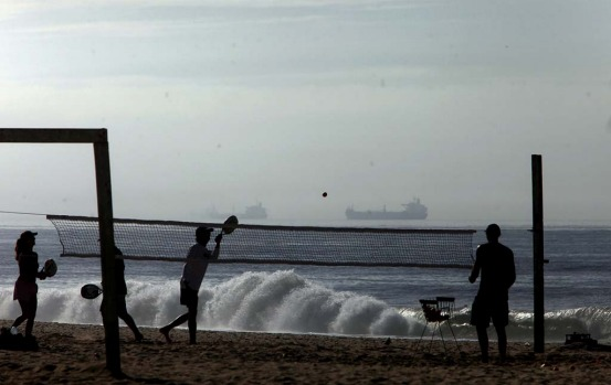 People play paddle ball on Ipanema beach as cargo ships wait to dock at Guanabara Bay in Rio de Janeiro.