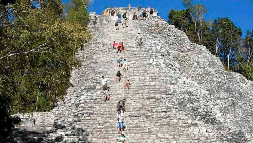 Tourists climb the Maya pyramid of Nohoch Mul at the archaeological site of Coba.