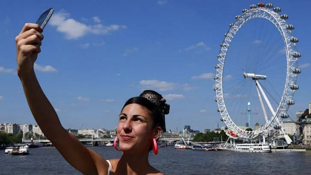 A tourist takes a snap of herself at the London Eye. It may be expensive, unfriendly and dirty, but travellers still rate London as the best city in the world.