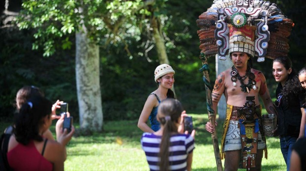 Tourists take pictures with a man dressed in a Mayan costume in the Tikal archaeological site in Peten departament 560 km north of Guatemala city on December 20, 2012. Ceremonies will be held here to celebrate the end of the Mayan cycle known as Bak'tun 13 and the start of the new Maya Era on December 21.