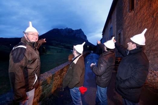 People gather at dusk in Bugarath, a small village in the foothills of the Pyrenees on December 20, 2012 in Bugarach, ...