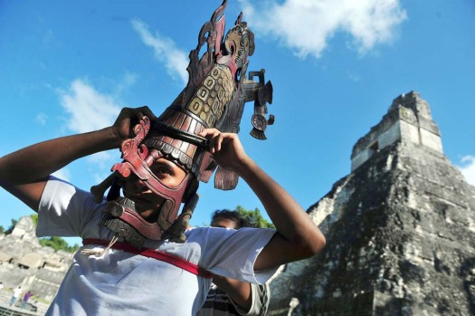A member of a folklore group places a Mayan mask on his head in front of the Mayan temple Gran Jaguar in the Tikal ...