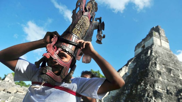 A member of a folklore group places a Mayan mask on his head in front of the Mayan temple Gran Jaguar in the Tikal archaeological site in Peten departament 560 km north of Guatemala city on December 20, 2012. Ceremonies will be held here to celebrate the end of the Mayan cycle known as Bak'tun 13 and the start of the new Maya Era on December 21.