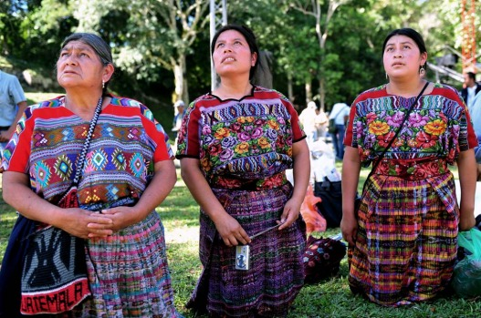 Guatemalan Maya natives kneel in front of a temple at Tikal archaeological site in Peten departament 560 km north of ...