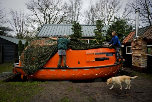 Duch Pieter van der Meer (L) and a friend uncover on December 19, 2012 his Norwegian lifeboat in his garden in ...