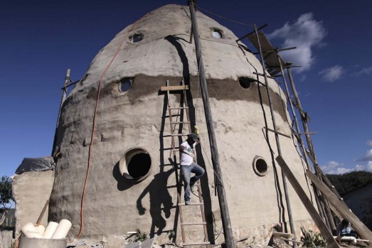 A laborer works on the construction of a house shaped like a spaceship and is designed by Augusto Vinholis, a ...