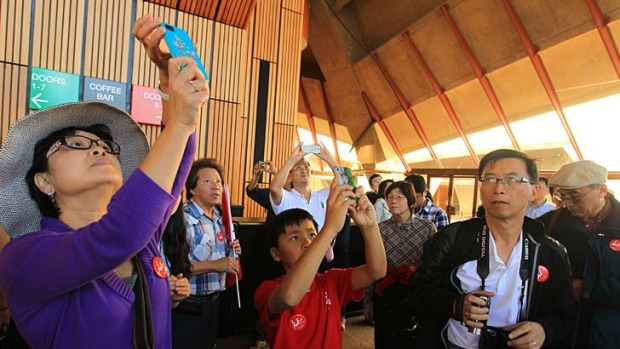 Pay-off at last … Chinese tourists, such as those seen here on a Mandarin tour of the Opera House in Sydney, are being drawn down under by a more China-friendly tourism industry.