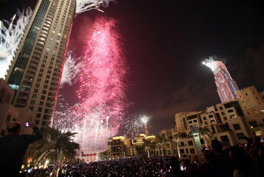 Fireworks illuminate Burj Khalifa while thousands of people gather to celebrate the New Year at midnight in Dubai.