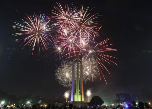 Spectators watch a fireworks display at the Quezon Memorial Circle in suburban Quezon city, north of Manila, Philippines.