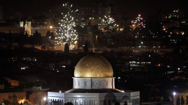 The golden dome of the Dome of the Rock is seen as fireworks light the skies of Jerusalem.