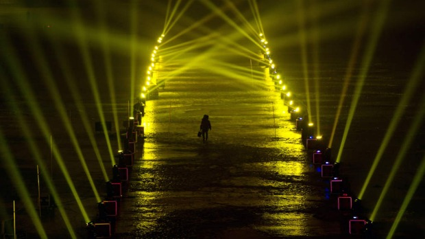 A reveller walks on a frozen lake between spotlights during a count-down event for the new year in Beijing.